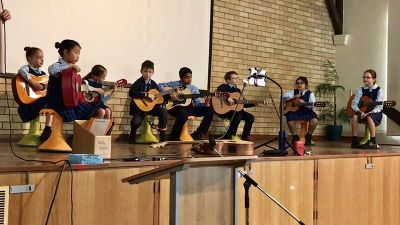 in-school guitar groups perform at school assembly
